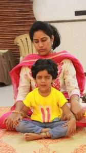 The little one trying to do prcatice Sukhasana with her mother.