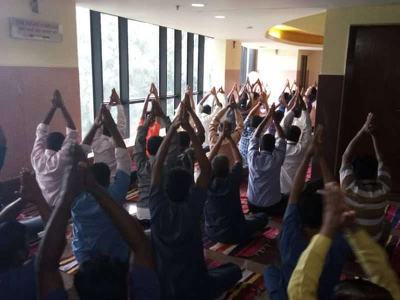 Employees doing Parvatasana.