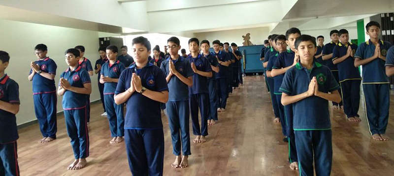Students of Swami Vivekanand School stand still in stithaprathanasana.