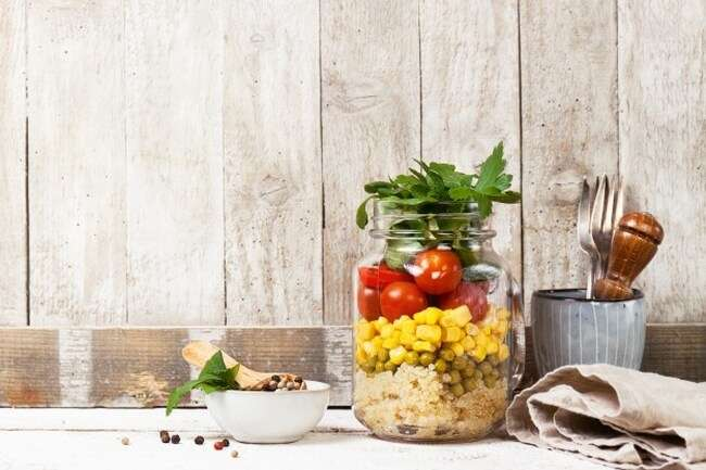 homemade-healthy-layer-salad-mason-jar-wooden-background